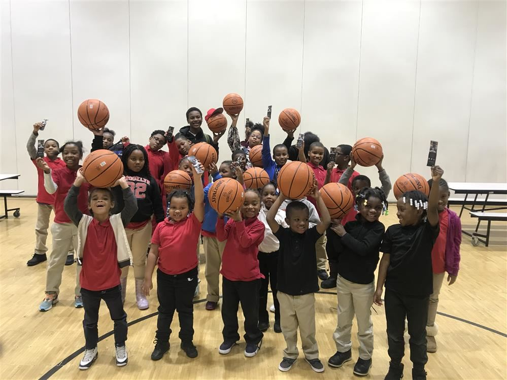 kids holding up basketballs and tickets