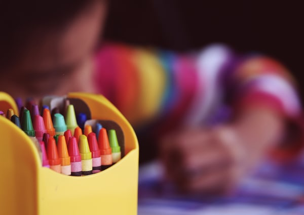 Box of crayons with a child coloring in the background