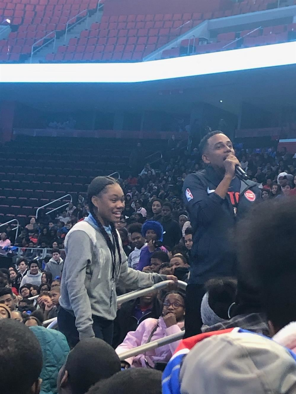 8th grade girl is standing with the announcer in Little Caesars Arena