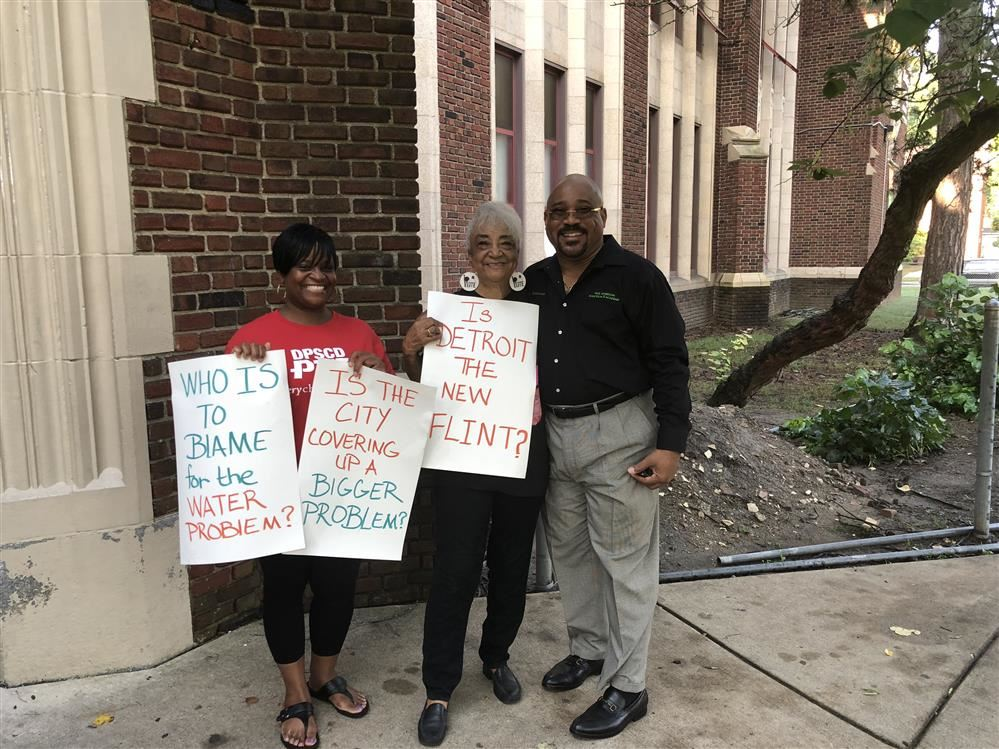 Principal, Dr.Robinson and members of the PTA holding signs about the schools water