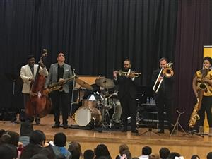 Jazz Band with people and instruments on stage with students on the floor watching