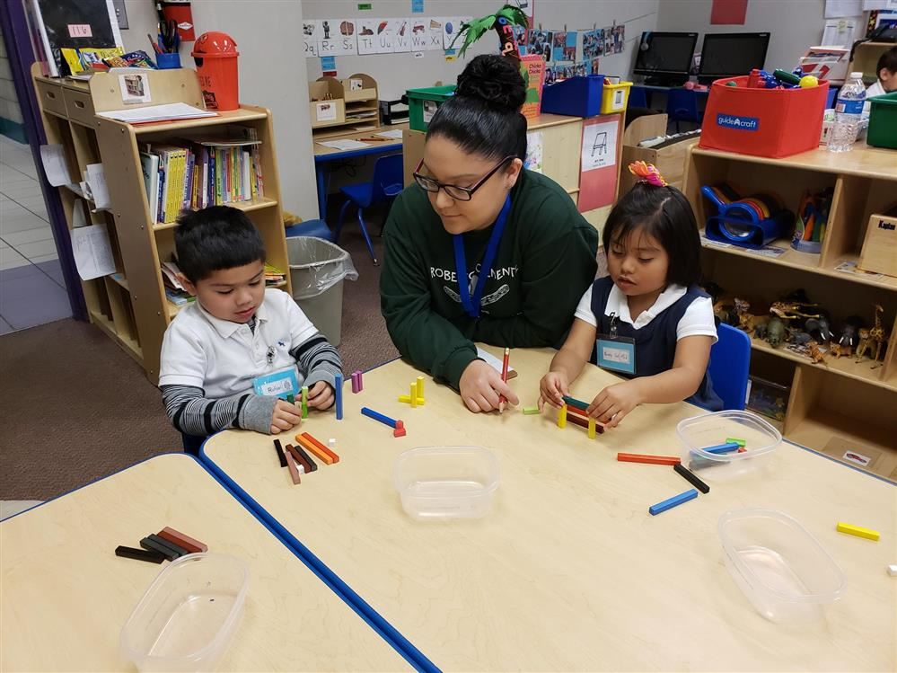 a picture of a boy, a teacher, and a girl at a table working with cuisenaire rods
