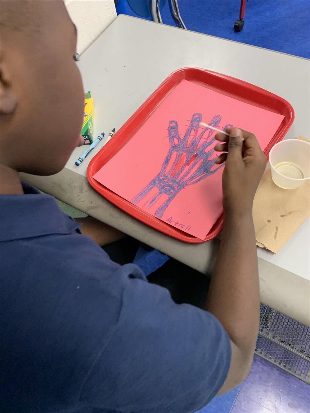Student painting a bones in a hand