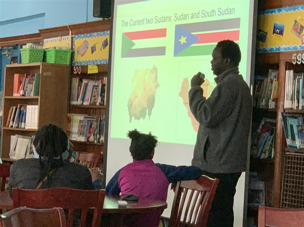 Man standing in front of projector screen with an image of Sudanese flag.