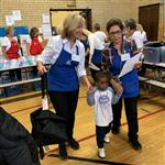 Two volunteers assist student during Operation School Bell
