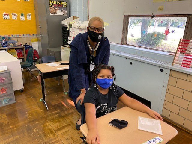 Principal Scott with a student both wearing a DPSCD mask