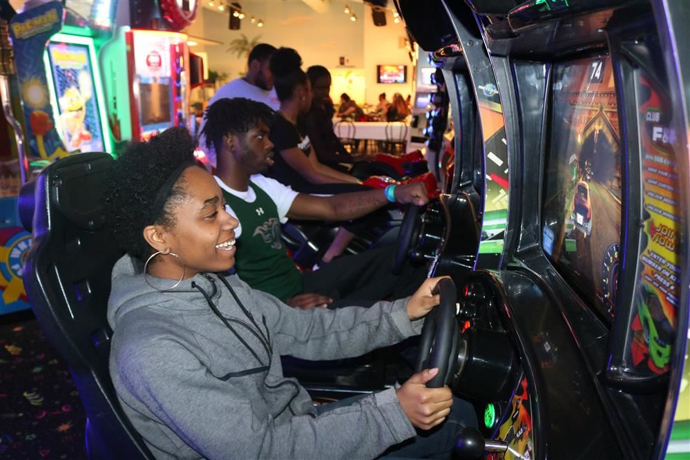 Two seniors race each other in an arcade car game at Paradise Park