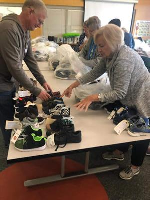 volunteers from St. Regis organizing shoes for give away