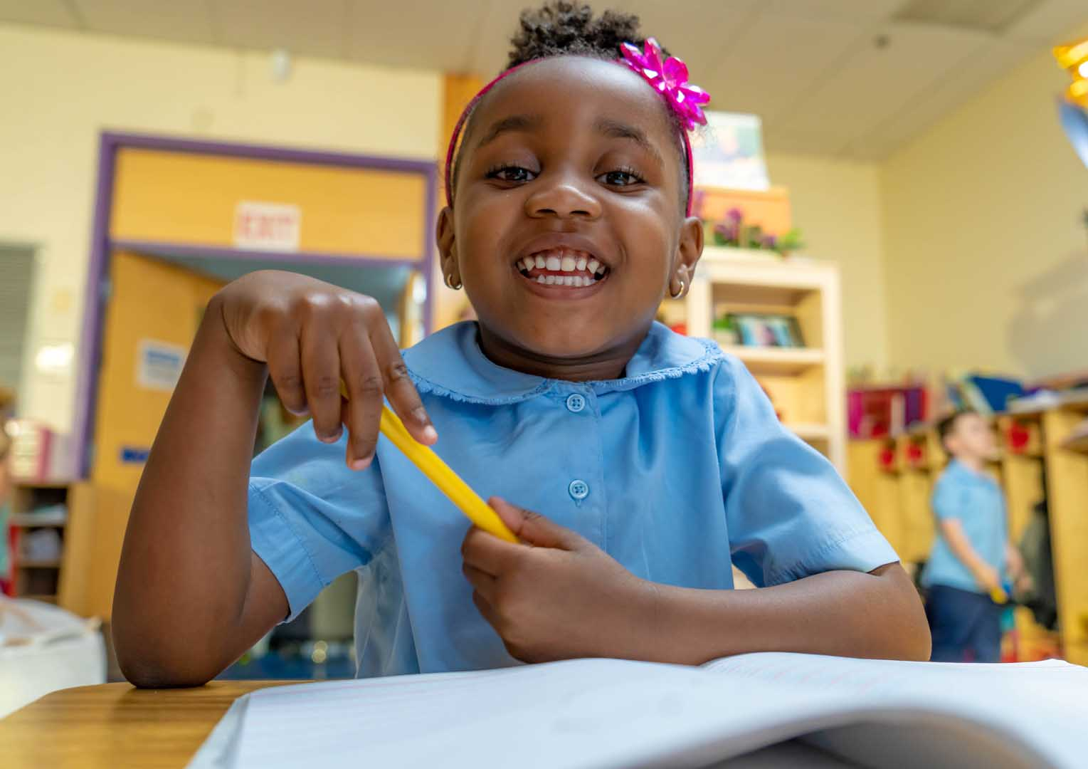 Little girl holding a pencil smiling